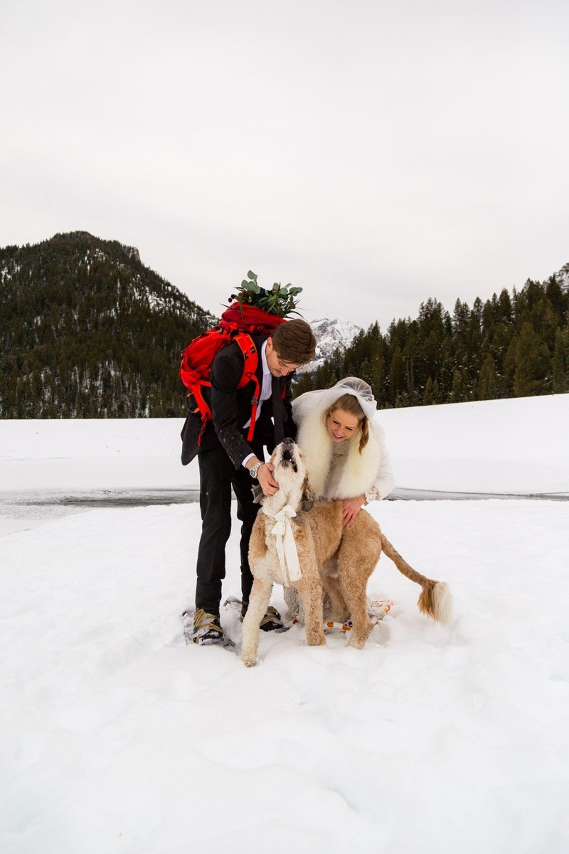 couple snowshoeing with their dog for their wedding day