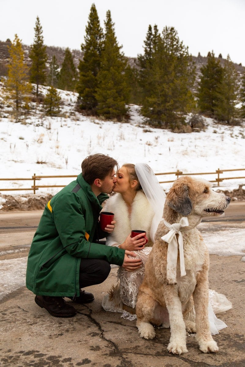 couple kissing while drinking coffee before their elopement