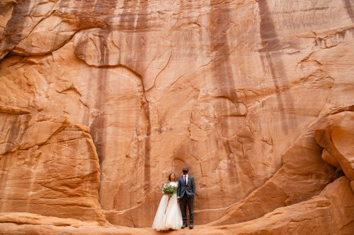 a couple stares up at the immense sandstone walls in Arches National Park during their elopement