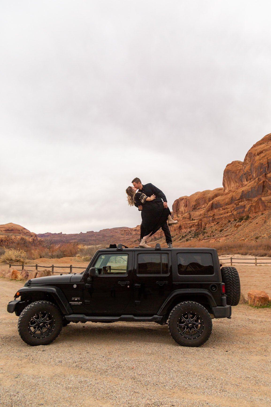couple on a black jeep in the moab desert. an adventure starts with a spark and a guidebook