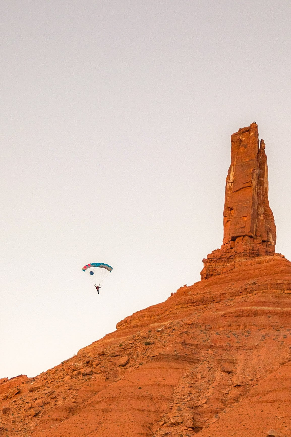 a base jumper floating off castleton tower in moab after climbing