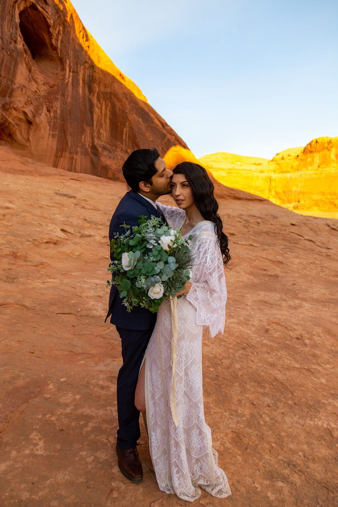 eloping couple at the corona arch in moab