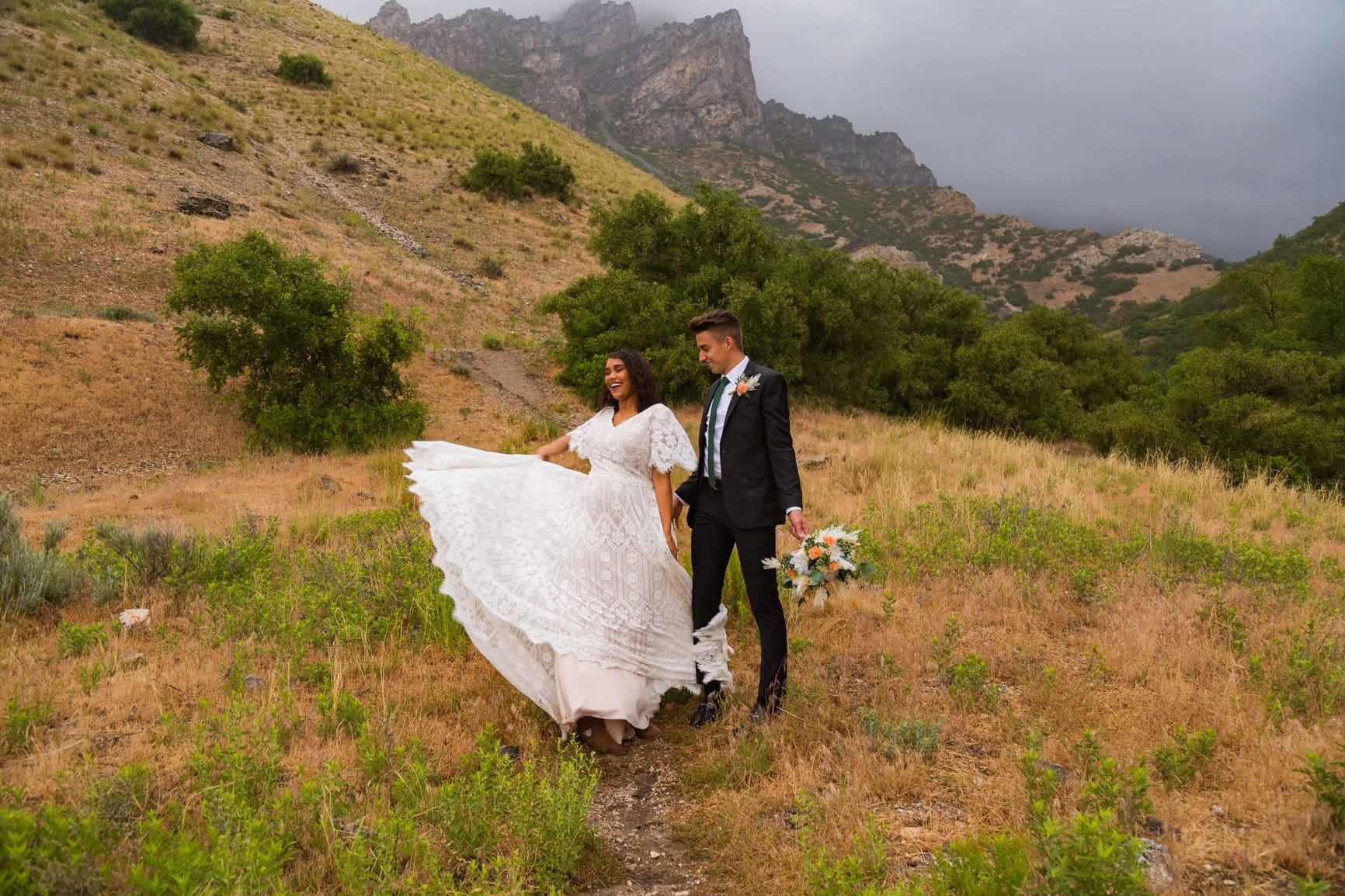 a bride flicks her beautiful dress skirt out in a field in provo canyon