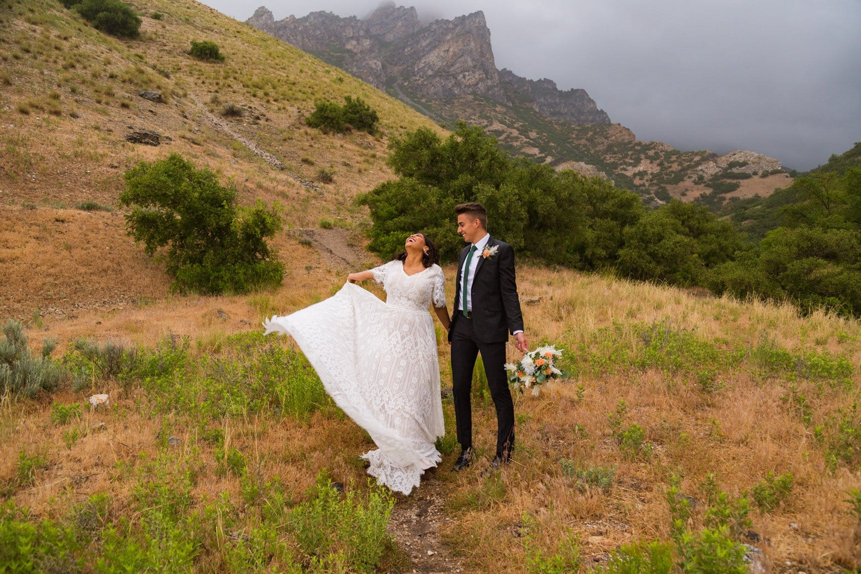 bride holds out her dress and takes in the rainy day in provo canyon