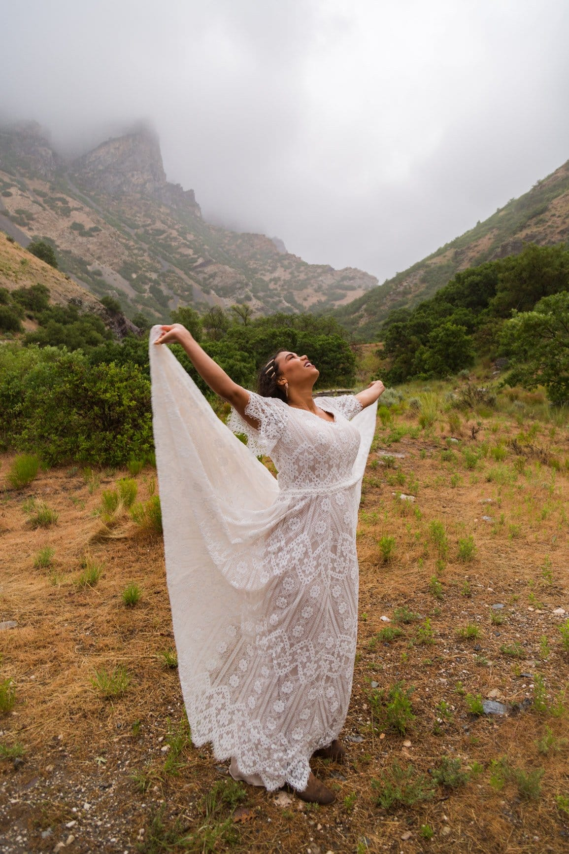 women dances in the rain among the foggy mountain peaks