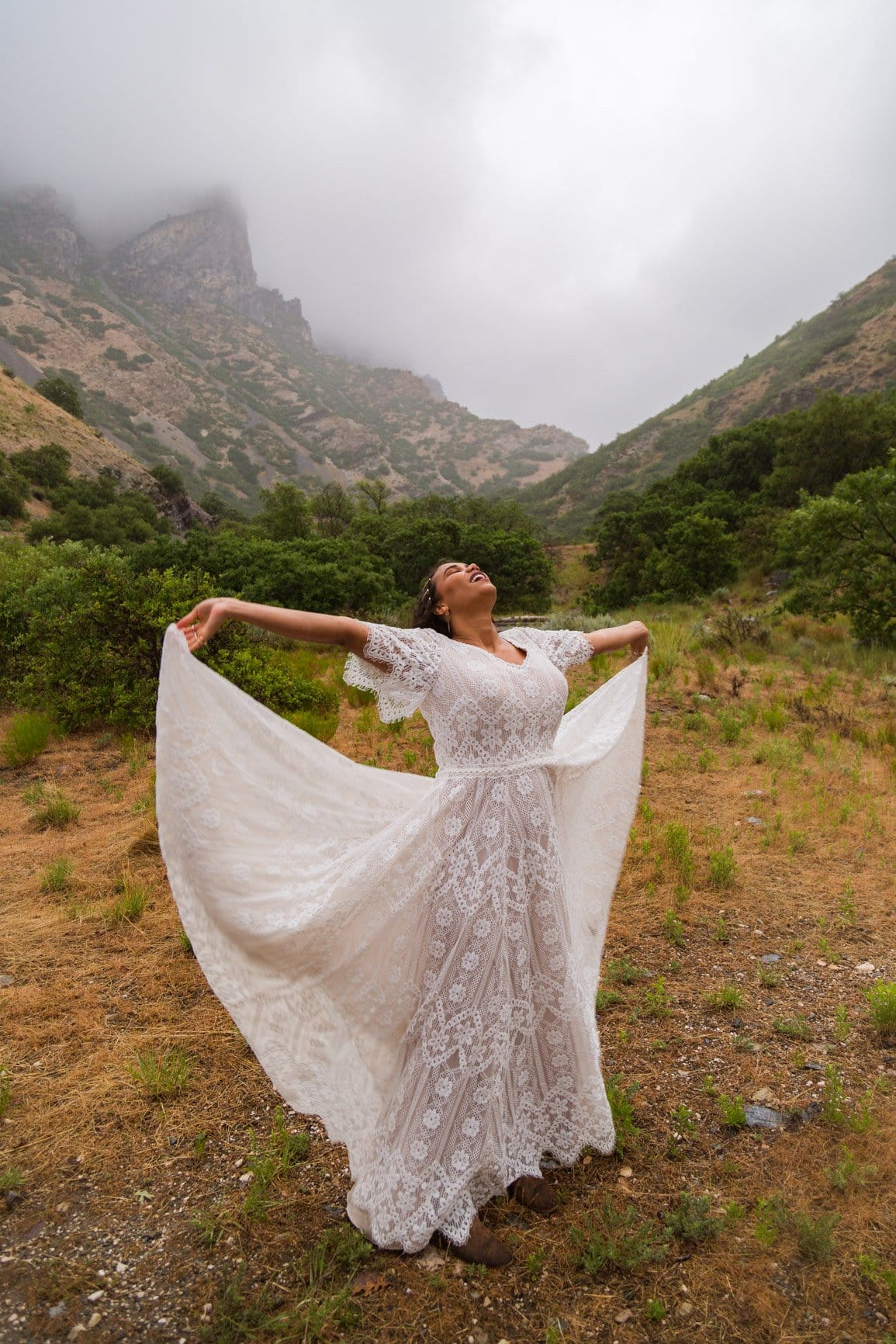 women outstretches her dress and takes in the wind and the rain