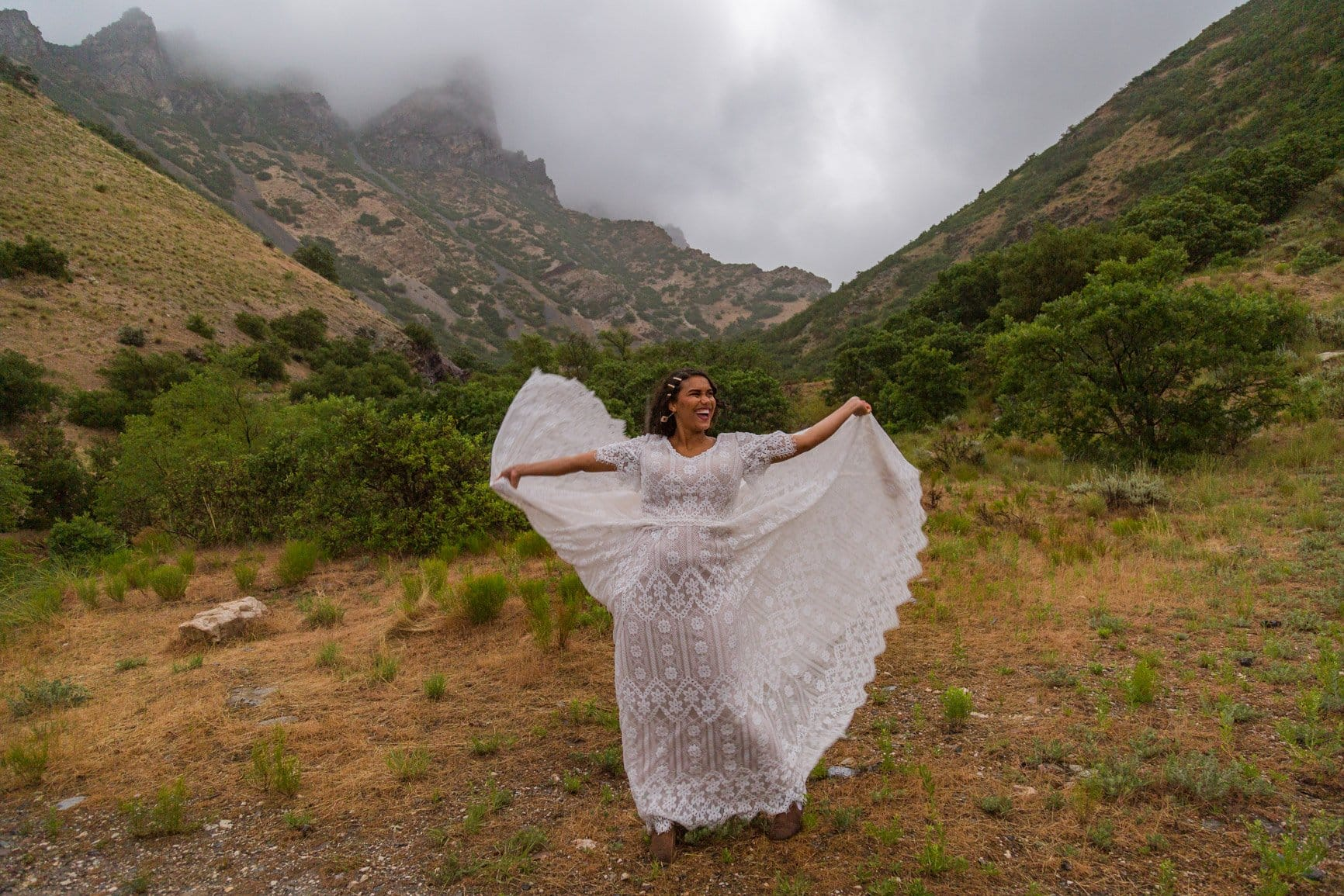 a women dances with her dress as the wind whips around her