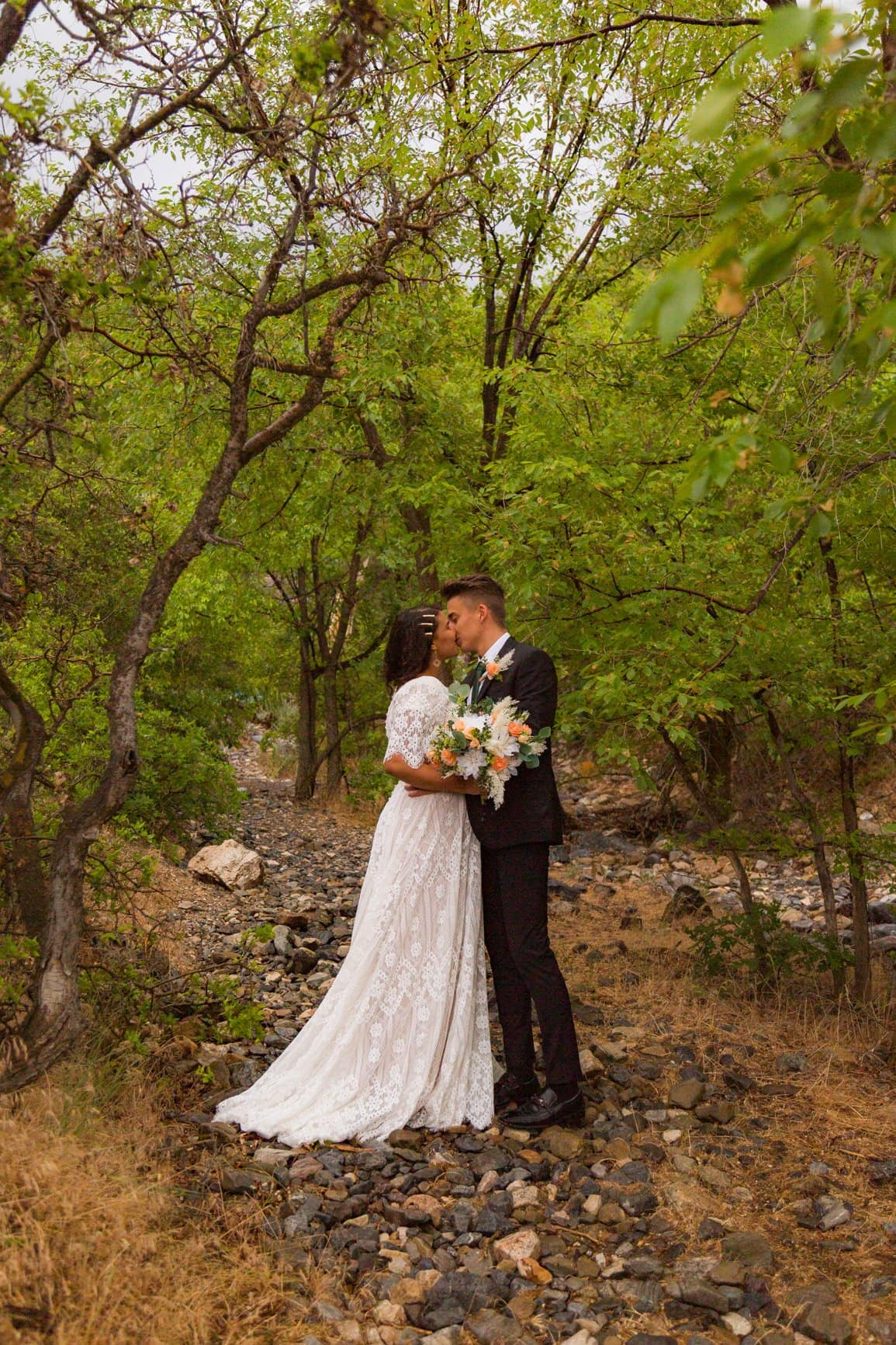 couple kisses in a forest in provo canyon