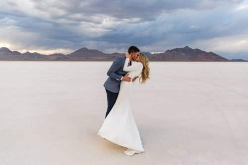 a couple kisisng on the bonneville salt flats in utah during their adventurous elopement