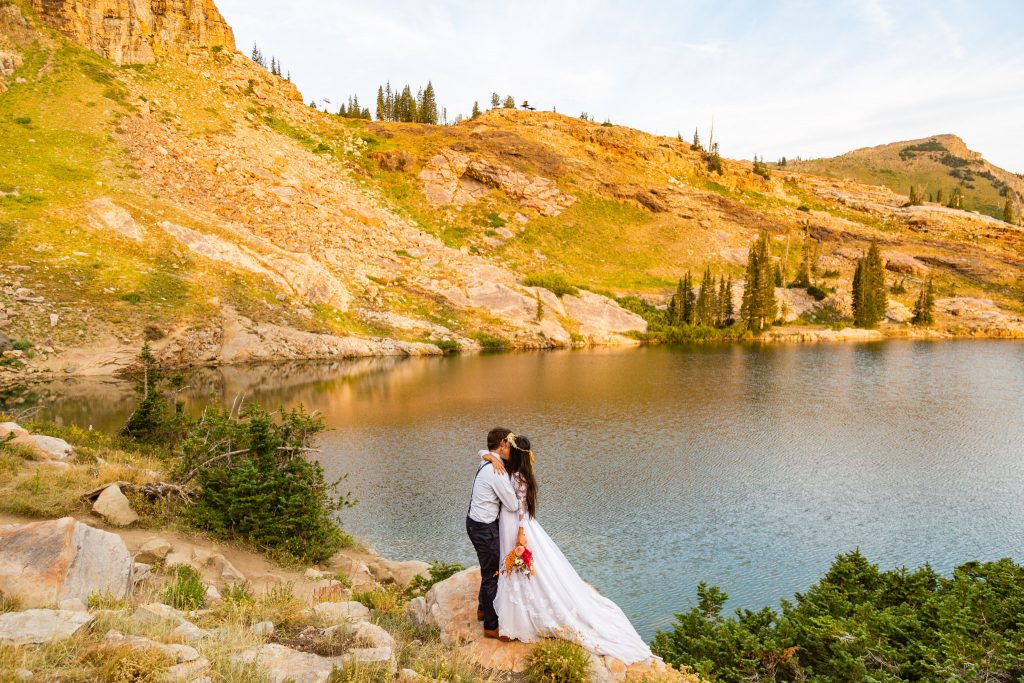 elopement at cecret lake in utah. A couple kisses by an alpine lake at sunrise