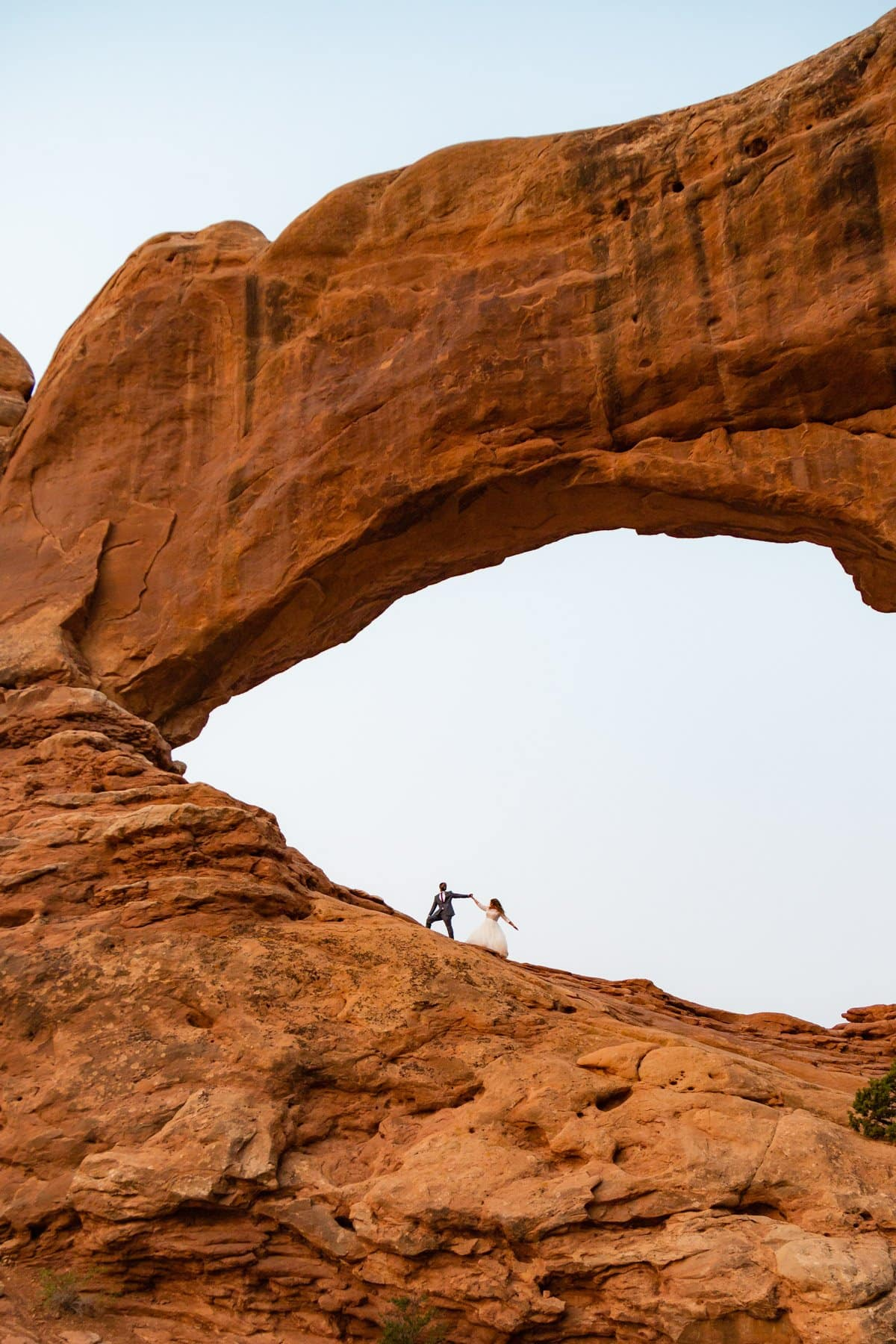 eloping couple hikes an arch in moab utah